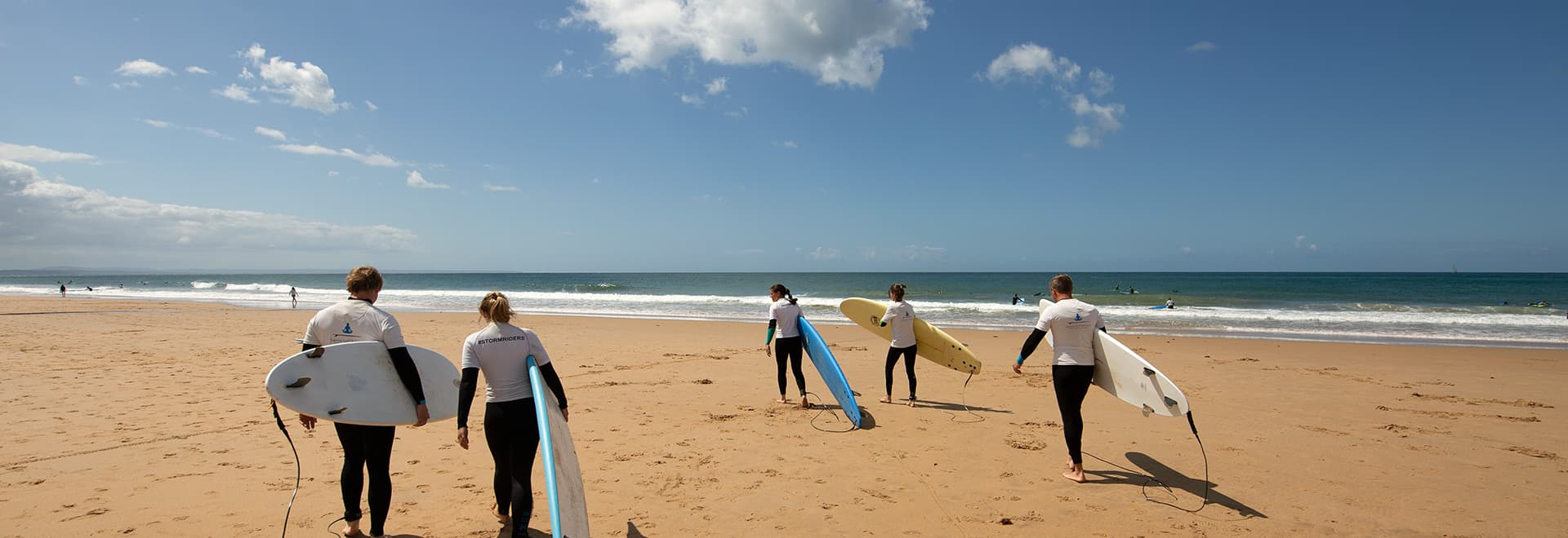intermediate group of surfers at the beach