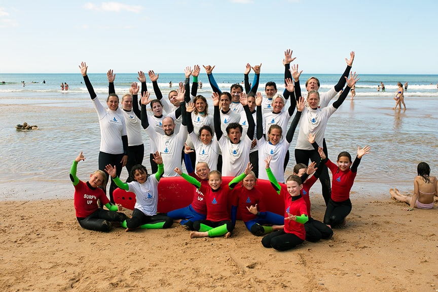 group of happy surf school clients at the beach